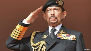 """Brunei's Sultan Hassanal Bolkiah salutes as the national anthem is played during celebrations for Brunei""""s 30th National Day, in Bandar Seri Begawan on 23 February, 2014"""