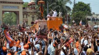 BJP's PM candidate Narendra Modi (C) gestures to supporters during a rally in Varanasi on April 24, 2014