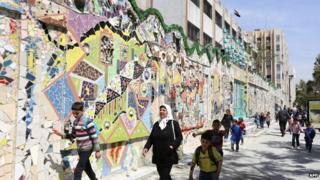 Syrian schoolchildren walk past a record-breaking mural in the al-Mazzeh neighbourhood