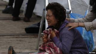 A relative of one of the missing passengers cries in Jindo