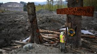 A man looks up at a sign commemorating the Oso mudslide on 21 April 2014