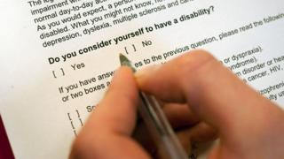 "A man's hand holds a pen hovering over a form, with the question ""Do you consider yourself to have a disability?"""