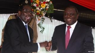 Zimbabwe President Robert Mugabe (L) jokes with Prime Minister Morgan Tsvangirai after signing Zimbabwe's new constitution into law, replacing a 33-year-old document forged in the dying days of British colonial rule and paving the way for elections, in Harare in this May 22, 2013 file photo.