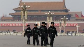 """Policemen patrol in front of the Tiananmen Gate and the giant portrait of China""""s late chairman Mao Zedong, at the Tiananmen Square near the Great Hall of the People after a plenary session of the NPC, in Beijing"""