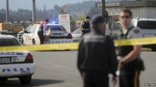Royal Canadian Mounted Police (RCMP) officers respond to the scene of a morning shooting at the Western Forest Products mill on Vancouver Island in Nanaimo, British Columbia, 30 April 2014