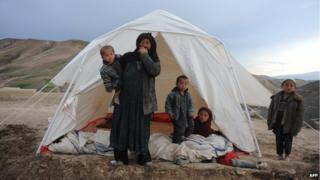 An Afghan woman with her children stands near her tent at the site of a landslide at the Argo district in Badakhshan, Afghanistan.