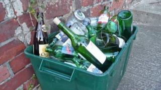A roadside recycling box containing bottles