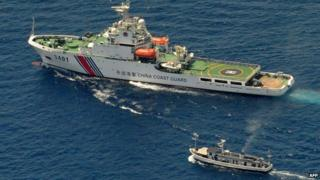 A China Coast Guard ship (top) and a Philippine supply boat engage in a stand off as the Philippine boat attempts to reach the Second Thomas Shoal, a remote South China Sea a reef claimed by both countries, on March 29, 2014.