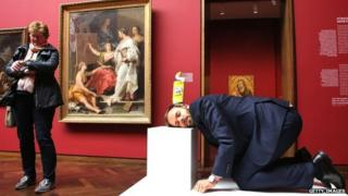 A man crouches with a bottle of toilet cleaner on his head at the Stadel Musuem, Frankfurt