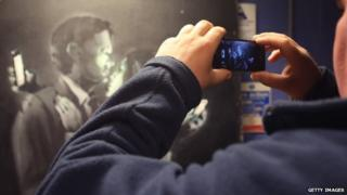 A mobile phone is used to take a picture of Banksy's Mobile Lovers artwork