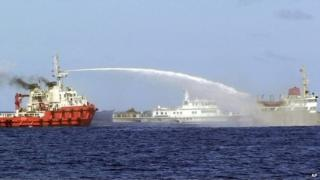 In this photo released by Vietnam Coast Guard, a Chinese ship, left, shoots water cannon at a Vietnamese vessel, right, while a Chinese Coast Guard ship, centre, sails alongside in the South China Sea, off Vietnam's coast, Wednesday, 7 May 2014