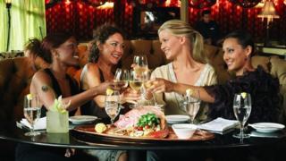 Four women sit around a restaurant's dinner table.
