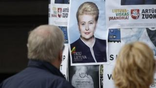 People look at an election poster of Dalia Grybauskaite in Vilnius