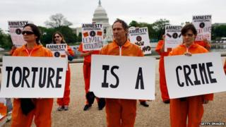 Activists from Amnesty International protest holding signs 'torture is a crime'