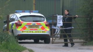 A police car and officer outside an industrial unit in Hampshire where a large quantity of stolen fuel was found