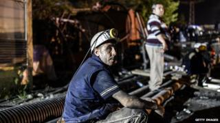 A miner sits outside a mine in Soma after a deadly explosion