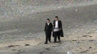 Two young Orthodox Jews walking on Aberystwyth seafront
