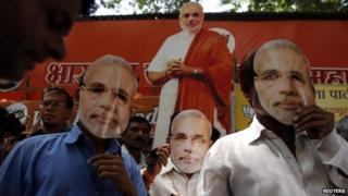 """Supporters of Hindu nationalist Narendra Modi, prime ministerial candidate for India""""s main opposition Bharatiya Janata Party (BJP), wear masks depicting Modi outside their party office in Mumbai"""