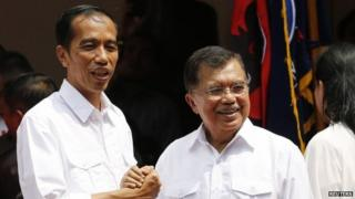 """Indonesian presidential candidate Joko """"Jokowi"""" Widodo (L) and his vice presidential running mate Jusuf Kalla shake hands during an event declaring their bid in the upcoming July 9 election, in Jakarta, 19 May 2014"""