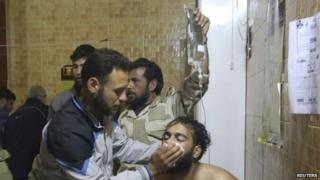 People treat a man affected by what activists say was a gas attack in Kfar Zeita village, inside a hospital in the central province of Hama (19 May 2014)