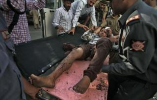 An Indian passenger who was injured after a private bus plunged off a mountain road into a deep gorge in the Indian portion of Kashmir is brought for treatment at the government medical college hospital in Jammu, India, Tuesday, May 20, 2014.