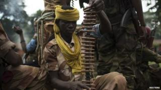 Former Seleka soldiers prepare to disembark from their vehicle in a village, where residents say was attacked and a mosque burnt the night before by anti-balaka militiamen, about 25 kilometres (16 miles) from Bambari on 10 May 2014