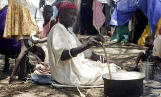 South Sudanese woman displaced by recent fighting prepares a meal