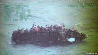 Handout image provided by the US Coast Guard showing approximately 100 Haitians sitting on the hull of a 40-foot sail freighter after it grounded and capsized on 26 November, 2013, 15 nautical miles southwest of Staniel Cay, Bahamas in the Caribbean Sea