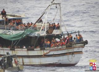 Italian sailors approach a boat carrying migrants off Sicily, 20 May