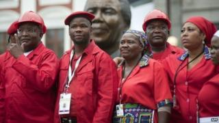 Members of the Economic Freedom Fighters(EFF) pose for a photo in front a bust of Nelson Mandela at the South African parliament on 21 May 2014