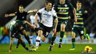 Craig Bryson of Derby County runs past Clint Hill and Richard Dunne of Queens Park Rangers