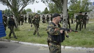 Armed pro-Russian men, wearing black and orange ribbons of St. George, a symbol widely associated with pro-Russian protests in Ukraine, gather near the body a man, whom armed men say was a representative of the Ukrainian far-right group Right Sector and killed in a fight, near a checkpoint on the outskirts of Donetsk on 23 May 2014.