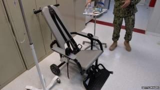 "This photo reviewed by the US military and made during an escorted visit shows a US naval medic explaining the ""feeding chair"" procedures at the detention facility in Guantanamo Bay, Cuba 9 April 2014"