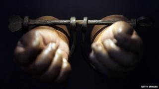 A photograph of a pair of hands in manacles.