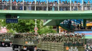 Paramilitary policemen ride on trucks during a parade in central Urumqi (23 May)