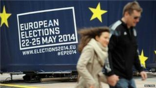 People walk in front of advert in Brussels (24 May)