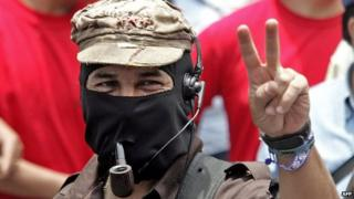 """Subcomandante Marcos flashes the """"v"""" sign as he takes part in a march in Mexico City, May 1, 2006."""