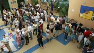 People queue to collect their ballot papers during voting in a presidential election at a polling station in on 25 May 2014.