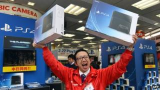 Salesman holding PS4 boxes