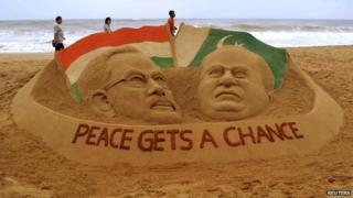 """People stroll past a sand sculpture of Indian Prime Minister-designate Narendra Modi (L) and Pakistan""""s Prime Minister Nawaz Sharif, created by Indian sand artist Sudarshan Patnaik on a beach in Puri, in the eastern Indian state of Odisha,on 25 May, 2014"""