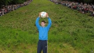 Josh Shepherd, 19, from Brockworth, celebrates winning the Men's Downhill race in the Cheese Rolling on Cooper's Hill