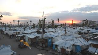 The sun sets on a row of tents used as temporary shelters by resident-survivors of super Typhoon Haiyan, along the coastal area of Tacloban City , Leyte province, in central Philippines on 15 February
