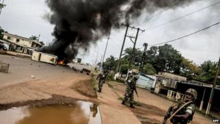 Burundian peacekeepers of the African-led International Support Mission to the Central African Republic (MISCA) patrol near a barricade of burning tyres erected in the Bea-Rex district of Bangui on 29 May 2014