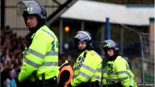 Police officers in riot gear at a football match
