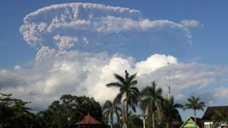 In this photograph taken on 30 May, 2014, a giant cloud of ash and steam rise from erupting Sangeang Api volcano seen from Bima town on Sumbawa island