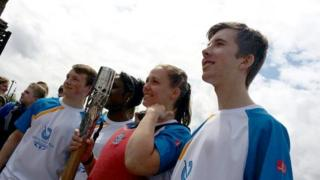 Torch bearers stand side by side in Bristol