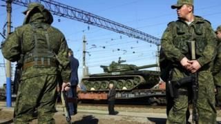 Armed Russian servicemen stand guard as Russian tanks arrive at a train station in the Crimean settlement of Gvardeiskoye