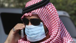 A man with mask speaks on his mobile phone in Jeddah May 29