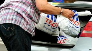 Shopper putting Tesco bags into a car