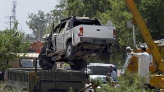 A damaged vehicle that carried military officers is removed from the site of suicide bombing on the outskirts of Fateh Jang, some 36 km (22 miles) southwest of Islamabad, Pakistan, Wednesday, June 4, 2014.